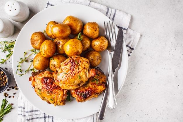 Gegrilltes hähnchen und ofenkartoffeln in einer gusseisernen pfanne. Premium Fotos