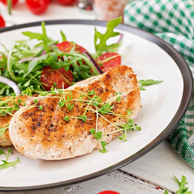 Gegrilltes hähnchenfilet und frischer gemüsesalat aus tomaten, roten zwiebeln und rucola. hühnerfleischsalat. gesundes essen. Kostenlose Fotos