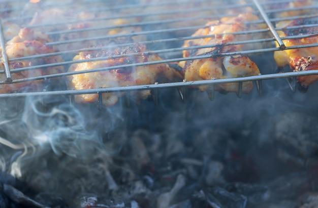 Gegrilltes hühnerbein über flammen auf einem grill. Premium Fotos