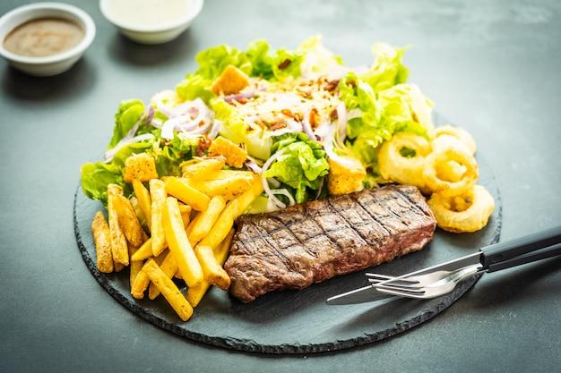 Gegrilltes rindfleischsteak mit pommes frites zwiebelring mit sauce und frischem gemüse Kostenlose Fotos