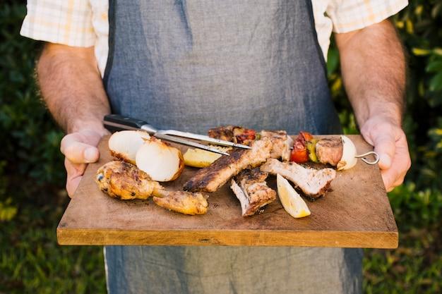 Gegrilltes saftiges fleisch und gemüse auf hölzernem schreibtisch in den händen Kostenlose Fotos