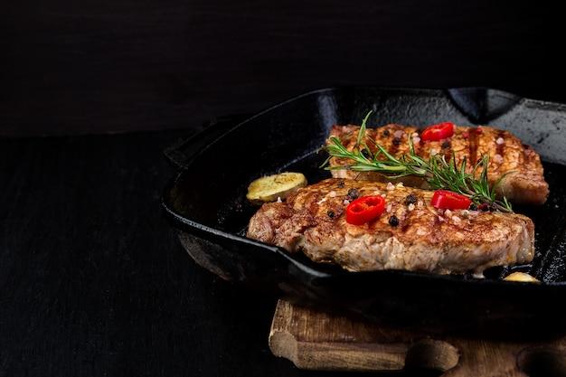 Gegrilltes schweinesteak in der grillpfanne mit rosmarin. Premium Fotos