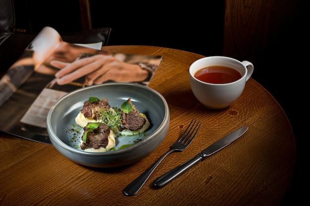 Gegrilltes steak mit gemüsepüree auf teller auf holztisch. Kostenlose Fotos