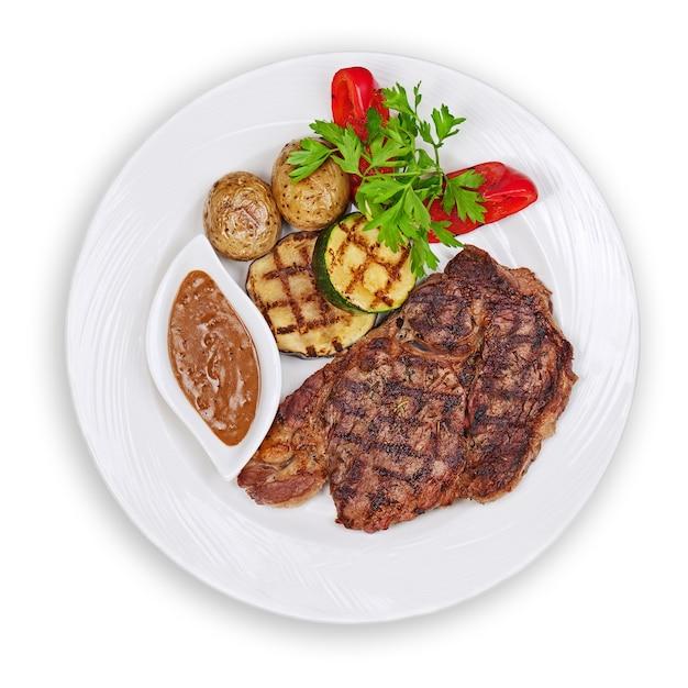 Gegrilltes steak, ofenkartoffeln und gemüse auf weißem teller isoliert. Premium Fotos
