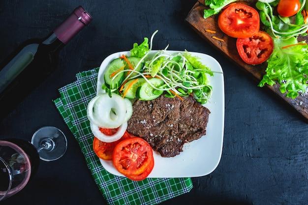 Gegrilltes steak und rotwein auf dem tisch Premium Fotos