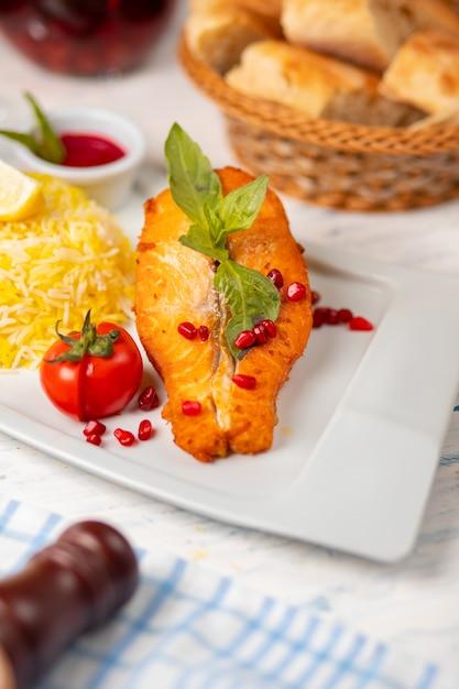 Gegrilltes weißes lachsfilet mit basilikum, tomaten und reis garnieren. Kostenlose Fotos