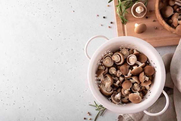 Gehackte waldpilze honig-agarics in einem weißen sieb, draufsicht Premium Fotos