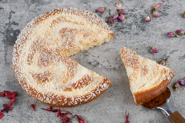 Gehackter runder köstlicher kuchen, der auf einen marmortisch gelegt wird. Kostenlose Fotos