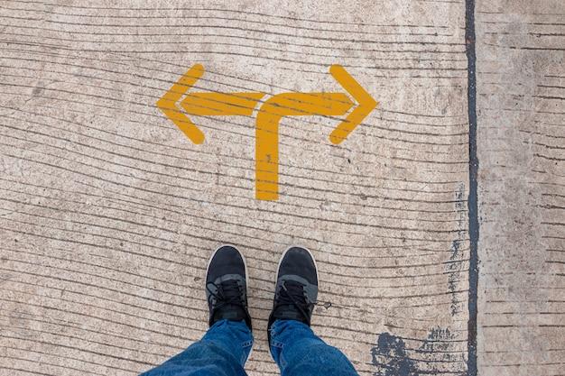 Gehe nach links oder rechts. ein mann, der auf der straße steht und über entscheidungen nachdenkt, wendepunktkonzept Premium Fotos