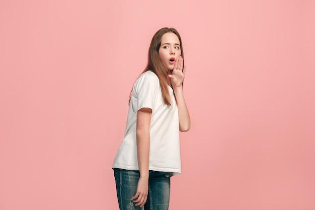 Geheimes klatschkonzept. junges jugendlich mädchen flüstert ein geheimnis hinter ihrer hand lokalisiert auf trendigem rosa. junges emotionales mädchen Kostenlose Fotos