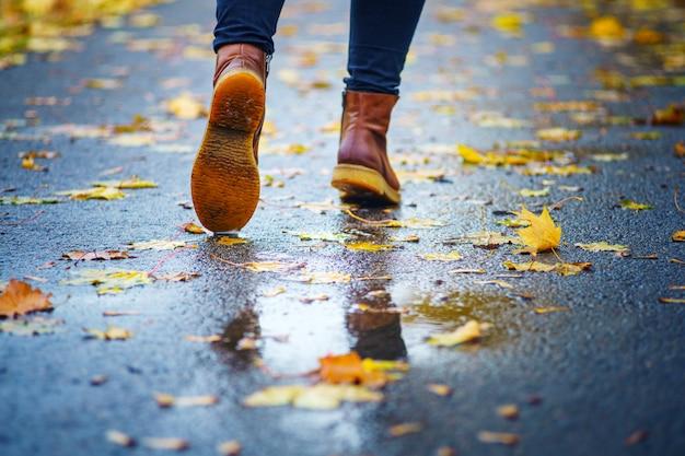 Gehen sie auf einem nassen bürgersteig. hintere ansicht über die füße einer frau, die entlang die asphaltpflasterung mit pfützen im regen geht der fall. abstrakter leerer freier raum des herbstes weathe Premium Fotos
