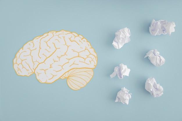 Gehirnausschnitt mit weißen zerknitterten papierbällen auf grauem hintergrund Kostenlose Fotos
