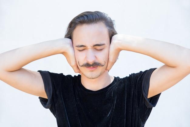 Gehörloser junger mann mit den geschlossenen augen, die ohren bedecken. Kostenlose Fotos