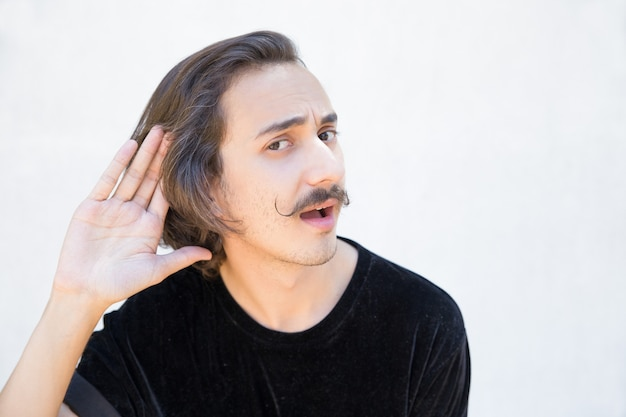 Gehörloser mann mit dem schnurrbart, der hand hinter ohr hüllt. Kostenlose Fotos