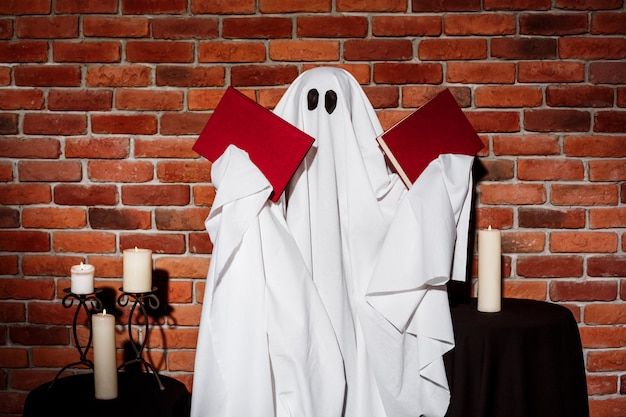 Geist hält bücher über mauer. halloween party. Kostenlose Fotos