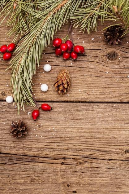 Geist-weihnachten auf holztisch. frische heckenrosenbeeren, ballsüßigkeiten, tannenzweige und zapfen, kunstschnee. naturdekorationen, hölzerne bretter der weinlese Premium Fotos