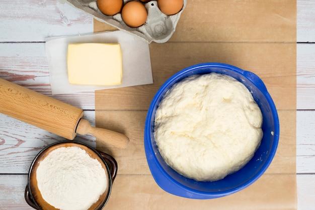 Gekneteter teig in blauer schale; eier; butter; mehl; und nudelholz auf schreibtisch aus holz Kostenlose Fotos