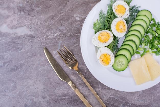 Gekochte eier mit gehackten kräutern und gurken in einem weißen teller Kostenlose Fotos
