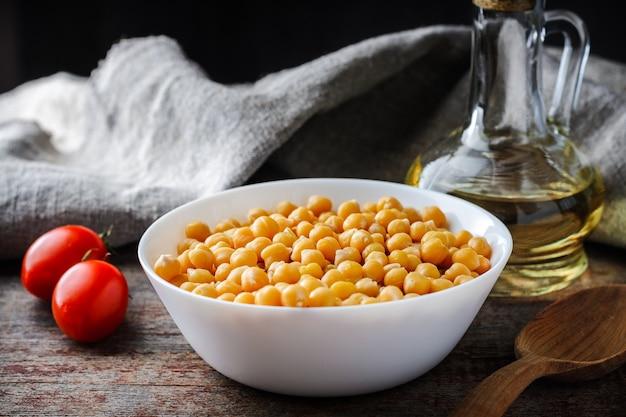 Gekochte kichererbsen in der platte, in den tomaten und im olivenöl auf einem holztisch Premium Fotos