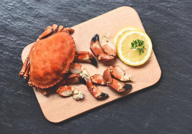 Gekochte krabben auf holzbrett mit zitrone auf schwarzem teller gekocht serviert meeresfrüchte red stone crab kralle Premium Fotos