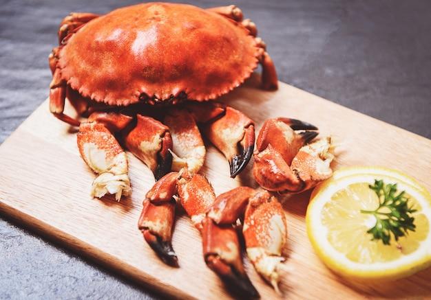 Gekochte krabben gekocht auf hölzernem brett mit zitrone auf schwarzblech Premium Fotos