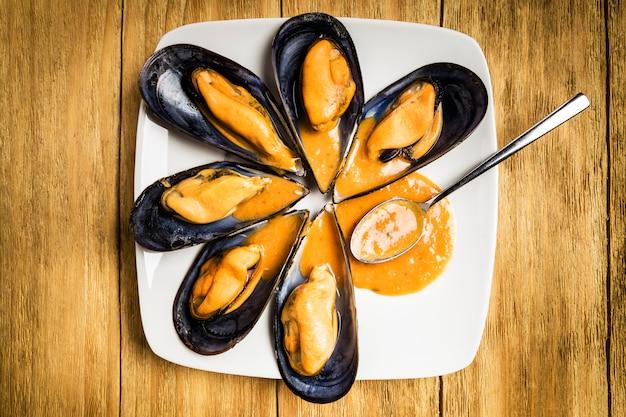 Gekochte miesmuscheln mit petersilie und orangensauce und eine halbe zitrone auf einer weißen platte Premium Fotos