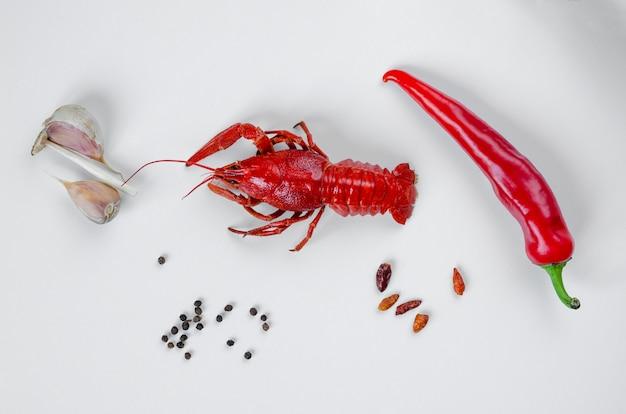 Gekochte rote krebse oder langusten mit roter paprika und knoblauch. food-minimalismus-konzept. Premium Fotos