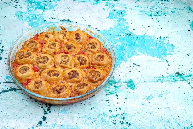 Gekochte teigmahlzeit mit hackfleisch und tomatensauce in der glaspfanne auf hellblauem backteig-fleischteig Kostenlose Fotos