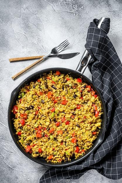 Gekochter bulgur mit gemüse und hühnerfleisch in einer pfanne. draufsicht Premium Fotos