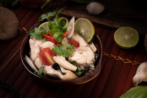 Gekochter fischaufguss mit tomaten, pilzen, koriander, frühlingszwiebeln und zitronengras in einer schüssel Kostenlose Fotos