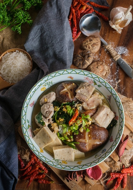 Gekochter reis mit schweinefleisch, pornoknochen und thailändischer schweinswurst in der schüssel Premium Fotos