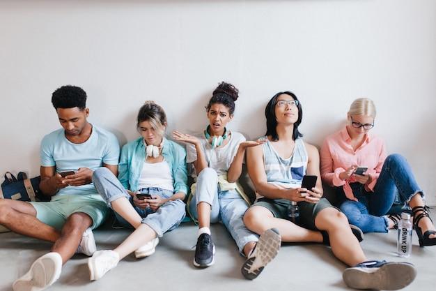 Gelangweiltes mädchen mit lockigen schwarzen haaren wütend, weil ihre college-freunde ihr nicht zuhören. müde internationale studenten sitzen auf dem boden und benutzen diese telefone nach der vorlesung. Kostenlose Fotos