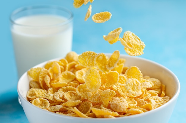 Gelb bereifte corn flakes rollen und ein glas milch zum trockenes, getreidefrühstück Premium Fotos