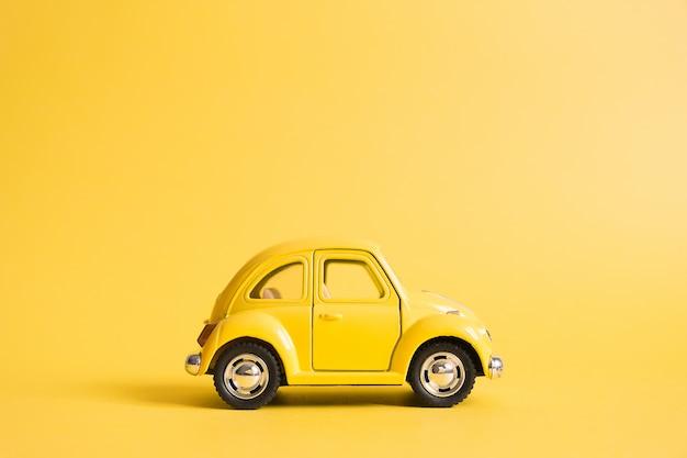 Gelb. retro spielzeugauto auf gelb. sommer reisekonzept. taxi Premium Fotos