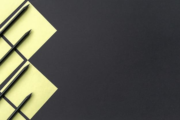 Gelbe aufkleber mit schwarzen stiften gezeichnet mit einem geometrischen muster auf schwarzem Premium Fotos