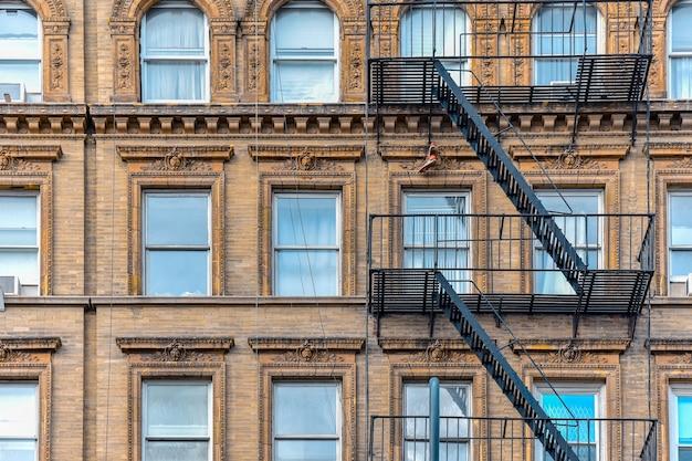 Gelbe backsteinfassade und ein paar stiefel, die von der feuertreppe hängen. chelsea, nyc. Premium Fotos
