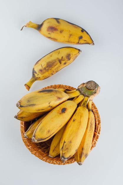 Gelbe bananen in einem weidenkorb auf weiß, Kostenlose Fotos