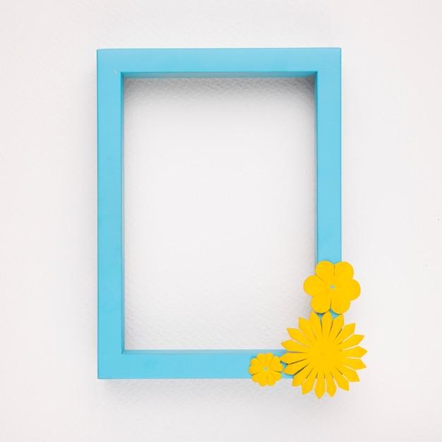 Gelbe blume auf dem hölzernen blauen rahmen gegen weißen hintergrund Kostenlose Fotos