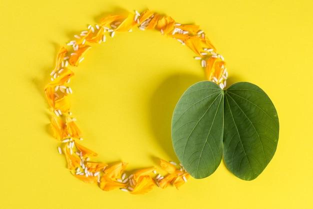 Gelbe blumen, grünes blatt und reis auf gelb Premium Fotos
