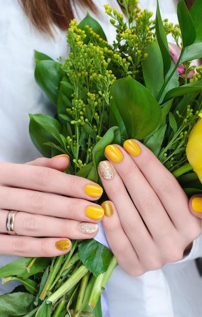 Gelbe blumen in frauenhänden. Premium Fotos