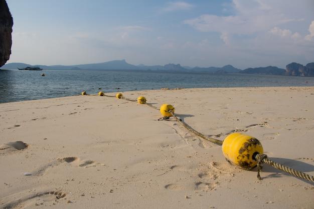 Gelbe bojen der nahaufnahme mit seil auf dem strand Premium Fotos