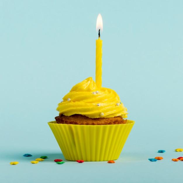 Gelbe brennende kerzen auf dekorativen muffins mit buntem stern besprüht gegen blauen hintergrund Kostenlose Fotos