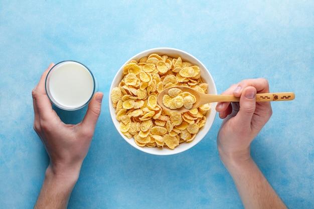 Gelbe corn flakes und ein glas milch zum trockenes frühstück. ansicht von oben. cerealien löffel und schüssel Premium Fotos