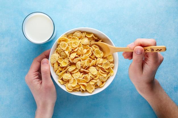 Gelbe corn flakes und ein glas milch zum trockenes gesundes frühstück. ansicht von oben. getreidelöffel und -schüssel in den händen Premium Fotos
