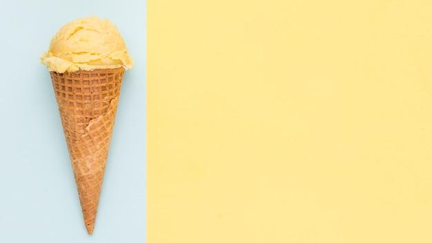 Gelbe eiscreme im oblatenkegel auf blauem und gelbem hintergrund Kostenlose Fotos