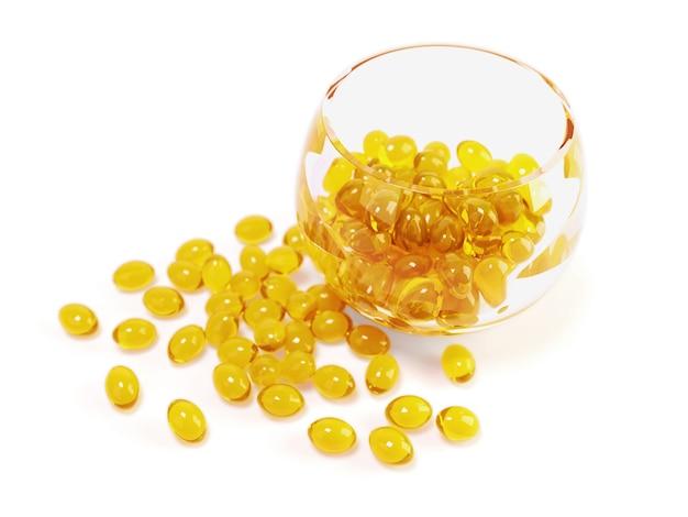 Gelbe fischölkapseln in der glasschüssel mit beschneidungspfad Premium Fotos
