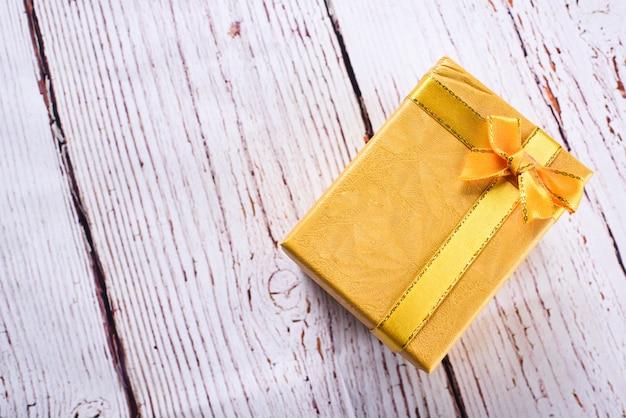 Gelbe geschenkbox mit schleifenband auf dem weißen holztisch, geburtstag, weihnachtstagskonzept. geschenkkonzept annehmen Premium Fotos