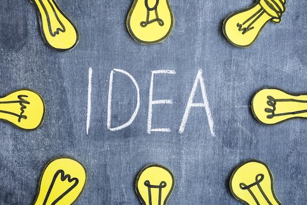 Gelbe glühlampen um den ideentext geschrieben auf tafel Kostenlose Fotos