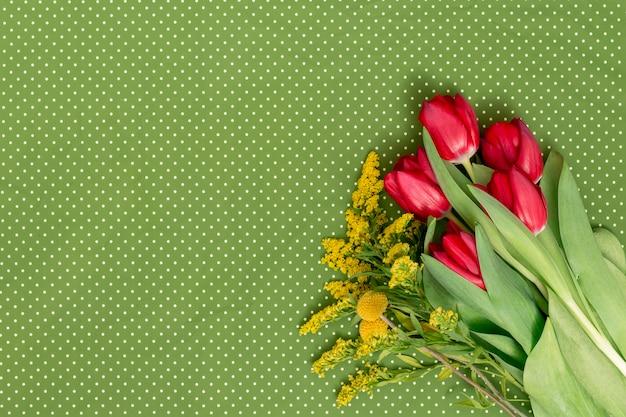 Gelbe goldrute und rote tulpe blüht auf ecke des grünen tupfenhintergrundes Kostenlose Fotos