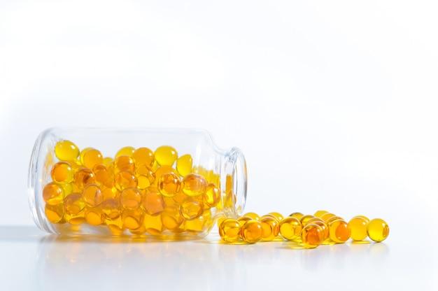 Gelbe kapseln zerstreuten von einem glasgefäß auf einem weißen hintergrund. Premium Fotos